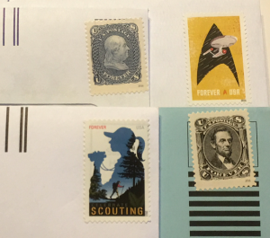 Four postage stamps on envelopes ready to mail